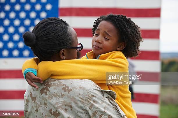 Returning Black soldier hugging daughter