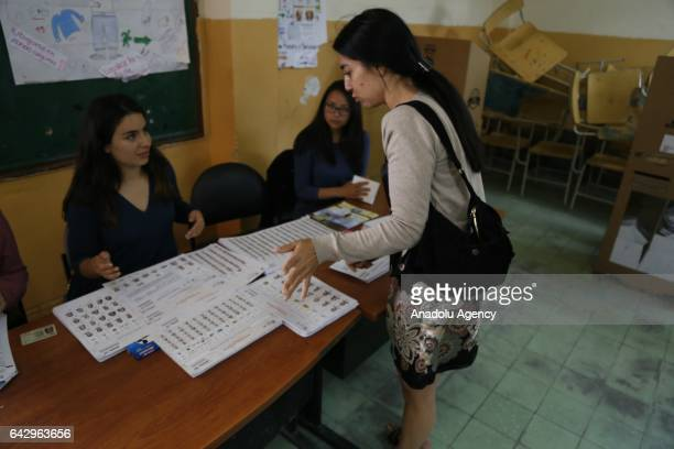 A returning officers checks the ID card of a voter during the general elections at a polling station in Quito Ecuador on February 19 2017