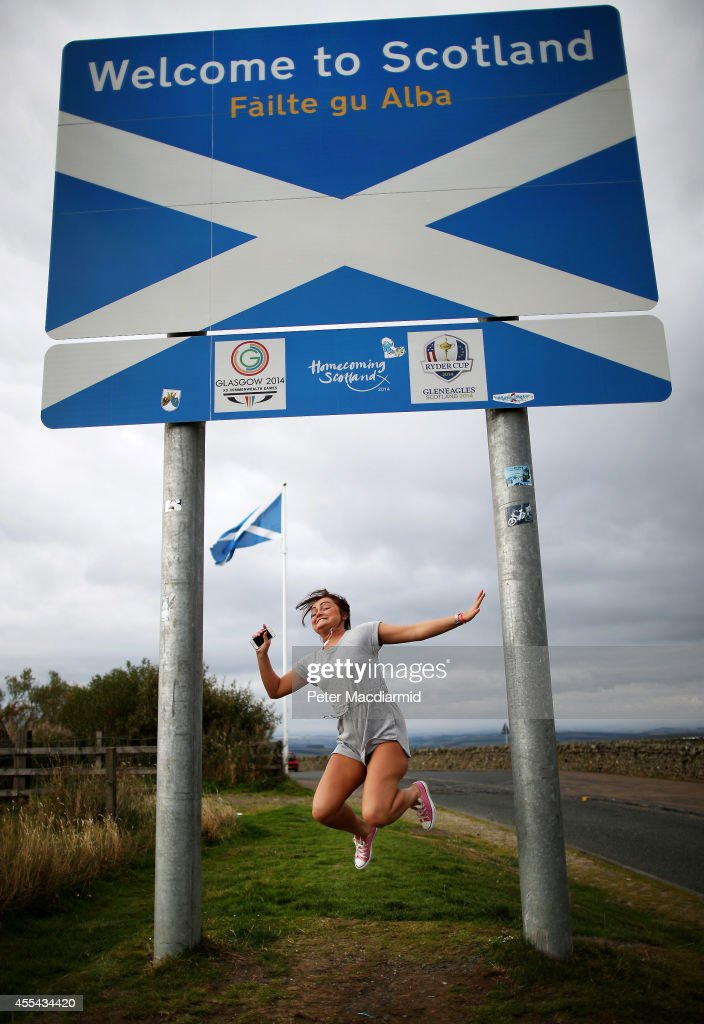 A returning Scottish woman jumps as her friend (out of shot) takes a photograph on the border with England on September 14, 2014 in Carter Bar, Scotland. The latest polls in Scotland's independence referendum put the No campaign back in the lead, the first time they have gained ground on the Yes campaign since the start of August.