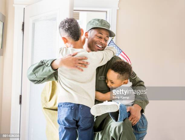 Returning soldier hugging children at door