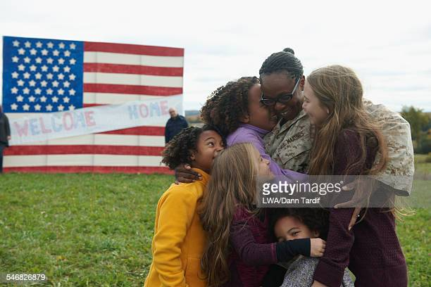 Returning soldier hugging family