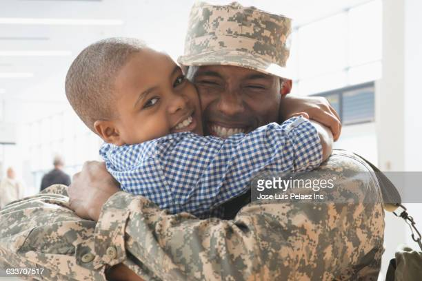 Returning soldier hugging son