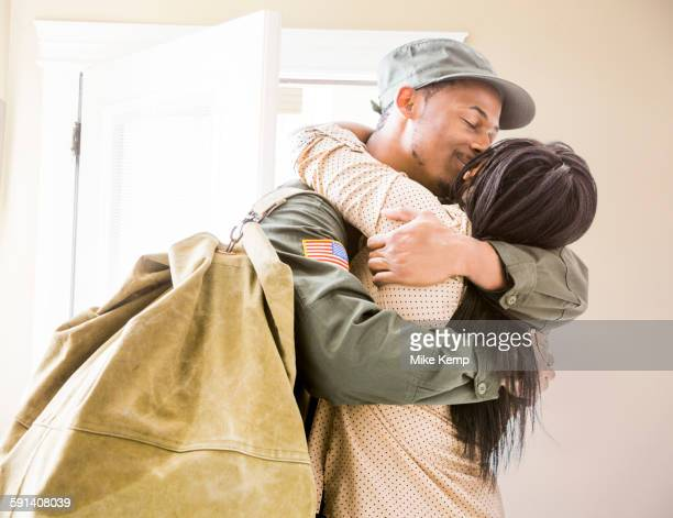 Returning soldier kissing wife in hallway