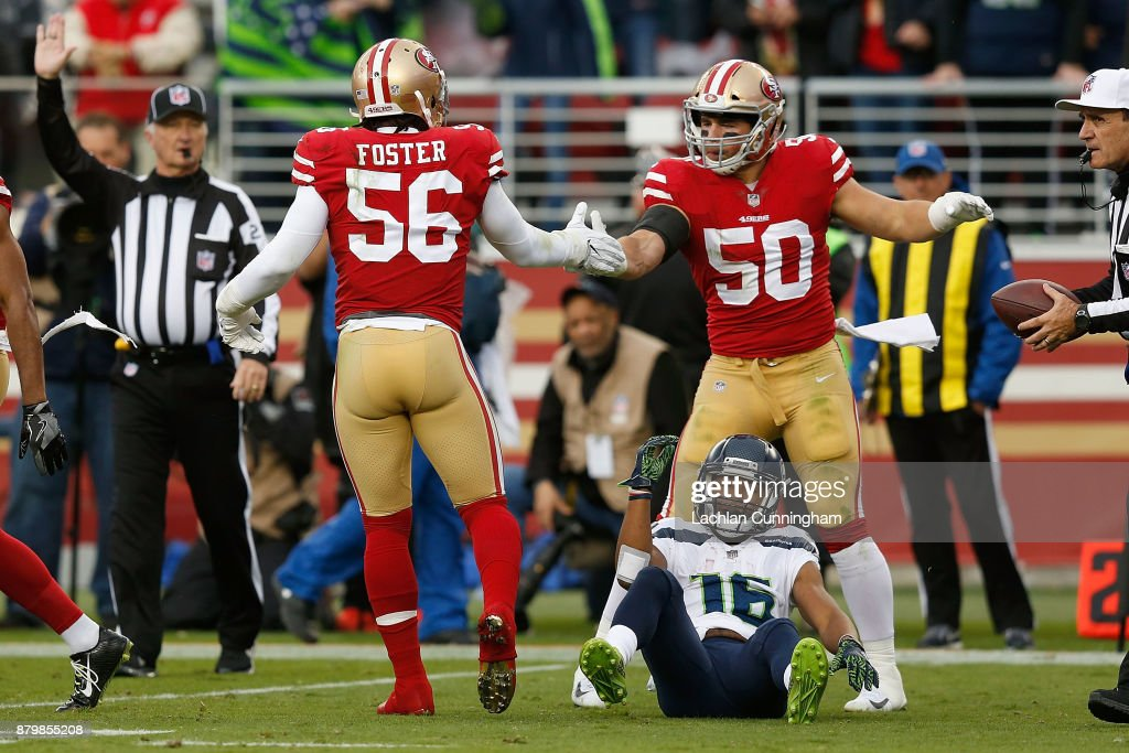 Reuben Foster #56 and Brock Coyle #50 of the San Francisco 49ers celebrate after tackling Tyler Lockett #16 of the Seattle Seahawks at Levi's Stadium on November 26, 2017 in Santa Clara, California.