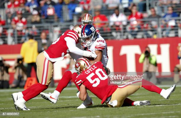 Reuben Foster and Brock Coyle of the San Francisco 49ers tackle Evan Engram of the New York Giants during the game at Levi's Stadium on November 12,...