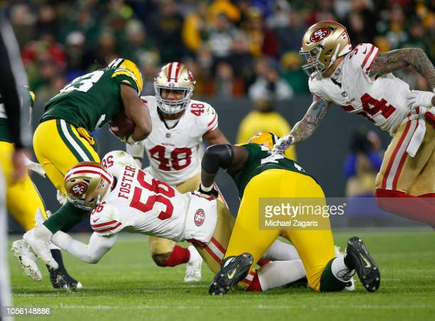 Reuben Foster and Fred Warner of the San Francisco 49ers tackle Aaron Jones of the Green Bay Packers during the game at Lambeau Field on October 15...