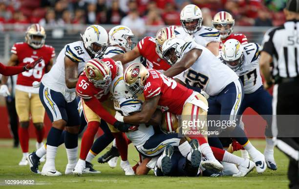 Reuben Foster, Brock Coyle and Ronald Blair III of the San Francisco 49ers team up for a tackle during the game against the Los Angeles Chargers at...