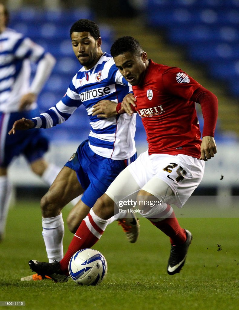 Reuben Noble-Lazarus of Barnsley holds off pressure from Jobi McAnuff of Reading during the Sky Bet Championship match between Reading and Barnsley at Madejski Stadium on March 25, 2014 in Reading, England,