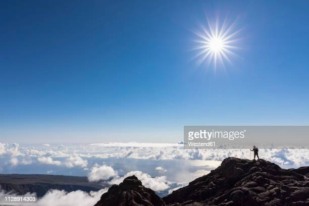reunion, reunion national park, shield volcano piton de la fournaise, female tourist hiking to crater - shield volcano stock pictures, royalty-free photos & images