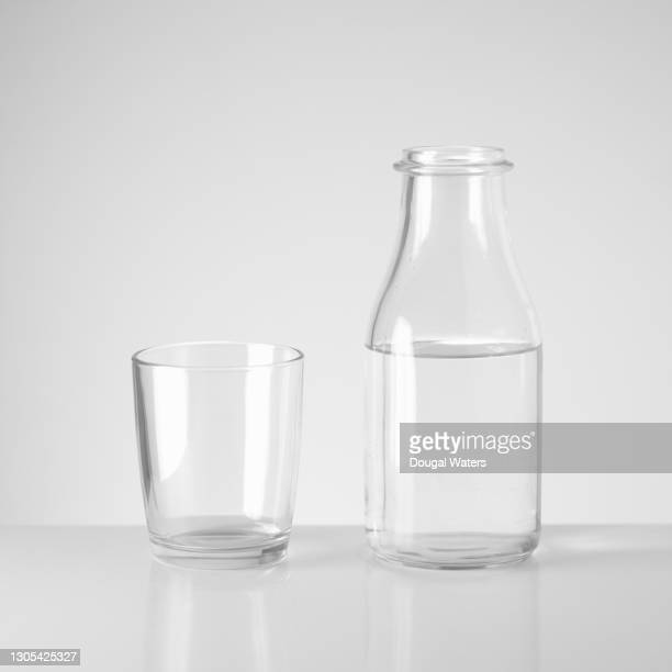 reusable glass bottle of water and drinking glass. - dougal waters stock pictures, royalty-free photos & images