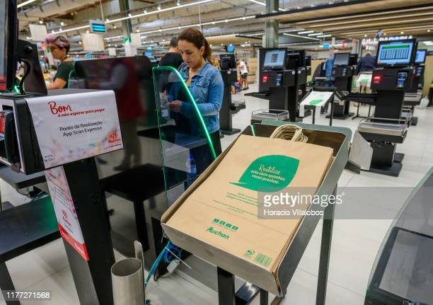 Reusable paper bags are seen next to shoppers using the express checkout machines in Auchan Hypermarket Alfragide a 13282 square meters store with...