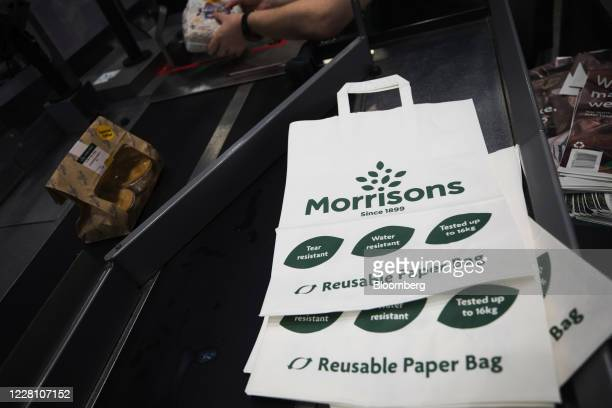 Reusable paper shopping bags sit on a check-out counter inside a Morrisons supermarket, operated by Wm Morrison Supermarkets Plc, in Saint Ives,...