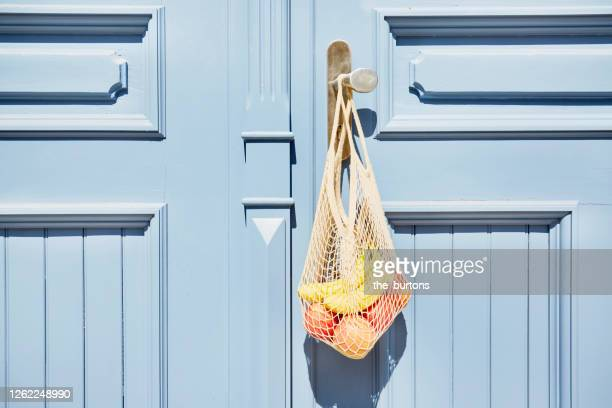 reusable shopping bag with apples and bananas hanging at blue wooden door - soziales thema stock-fotos und bilder