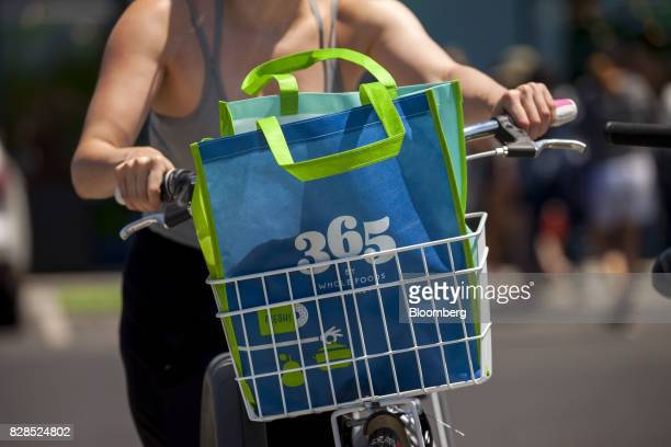 A reusable Whole Foods Market 365 shopping bag is seen in the bicycle basket of a customer during the grand opening of a Whole Foods Market 365...