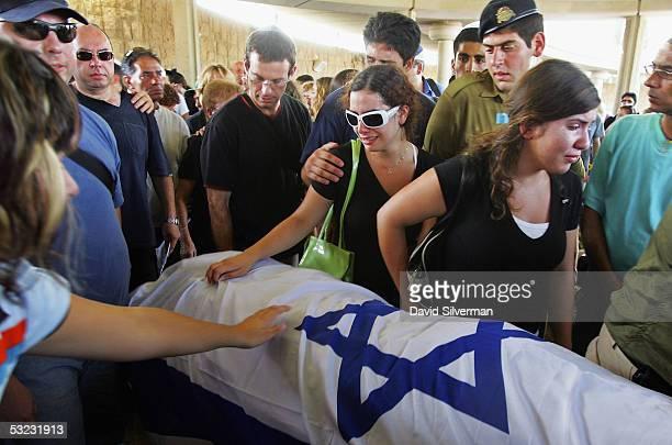 Reut Horvitz sister of 16yearold Israeli teenager Nofar Horvitz grieves over her flagdraped body during her funeral July 13 2005 at Tel Aviv's Yarkon...