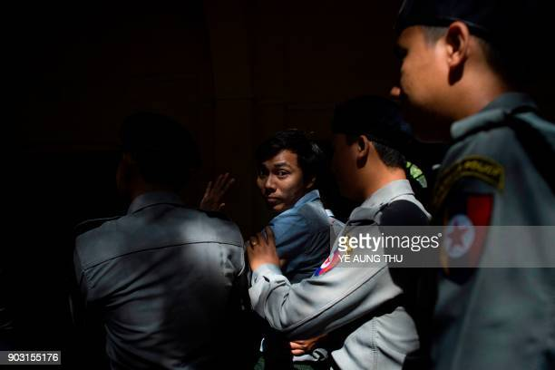 Reuters journalist Kyaw Soe Oo is escorted by police after a court appearance in Yangon on January 10, 2018. Myanmar police formally filed charges on...