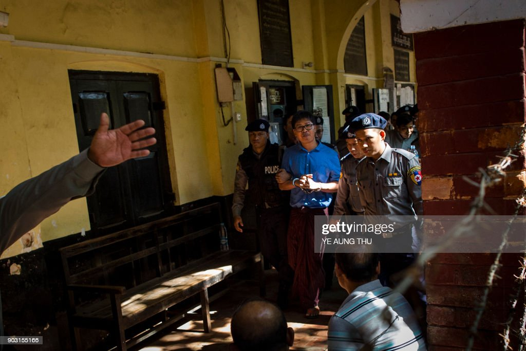 Reuters journalist Wa Lone (C) is escorted by police after a court appearance in Yangon on January 10, 2018. Myanmar police formally filed charges on January 10 against two Reuters reporters accused of breaching the Official Secrets Act, a judge said, an offence that carries up to 14 years in prison. /