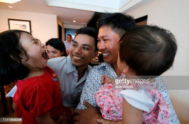 Reuters journalists Wa Lone and Kyaw Soe Oo carry their children after being freed from prison in a presidential amnesty in Yangon on May 7, 2019. -...