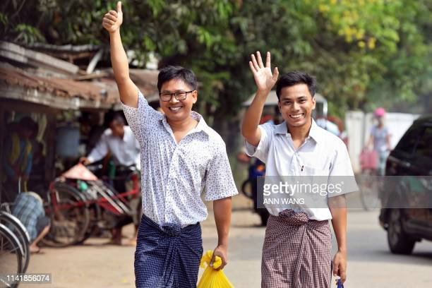 Reuters journalists Wa Lone and Kyaw Soe Oo gesture as they walk to Insein prison gate after being freed in a presidential amnesty in Yangon on May...