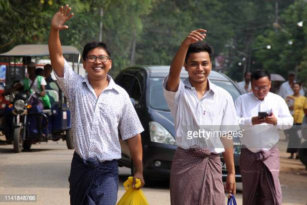 Reuters journalists Wa Lone and Kyaw Soe Oo gesture outside Insein prison after being freed in a presidential amnesty in Yangon on May 7, 2019.