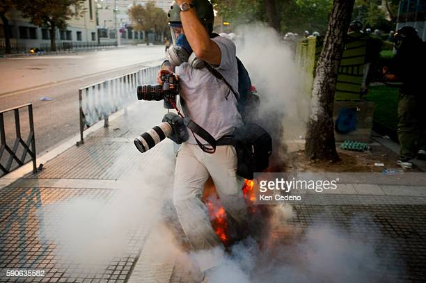 Reuters photographer Yannis Behrakis gets caught under a shock bomb during a protest in Thessaloniki, Greece Sept 11, 2011. Taxi cab drivers,...
