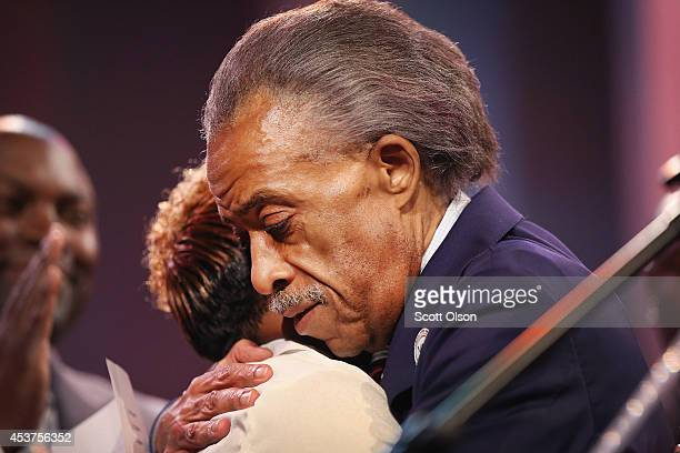 Rev Al Sharpton hugs Lesley McSpadden the mother of slain teenager Michael Brown during a rally at Greater Grace Church on August 17 2014 in Ferguson...