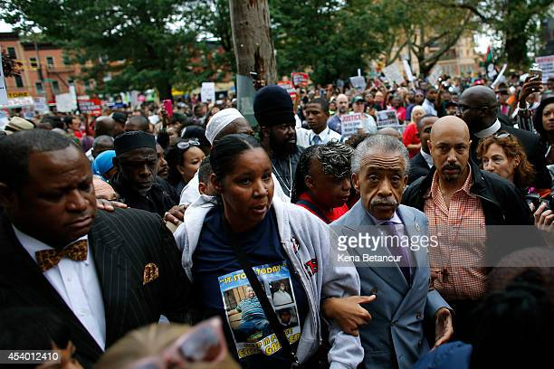 Rev Al Sharpton is joined by Esaw Garner wife of Eric Garner as they march during a rally against police violence on August 23 2014 in the borough of...