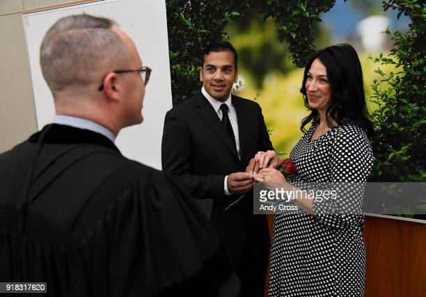 Rev Brian Henderson left officiates over the marriage of Shelan Shah center and his bride Valerie GaddisArellano at the 11th annual Valentine's Day...