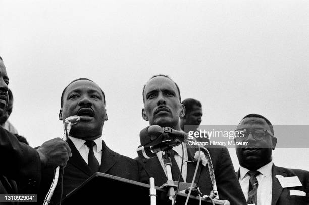 Rev Dr Martin Luther King Jr standing next to Albert Raby at a speakers podium during a march from Buckingham Fountain to City Hall to demonstrate...