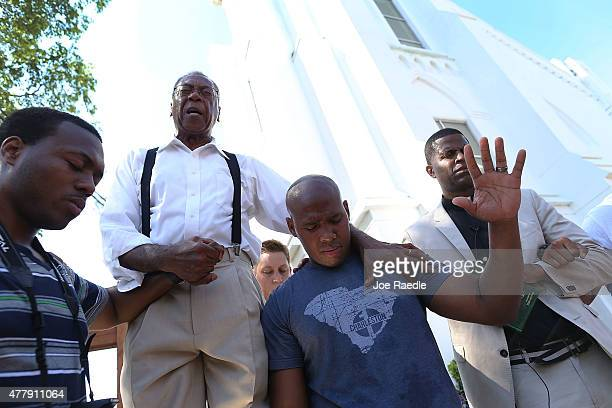 Rev Franklin Ferguson and Pastor Philip Pinckney join together to lead a group prayer in front of the Emanuel African Methodist Episcopal Church...