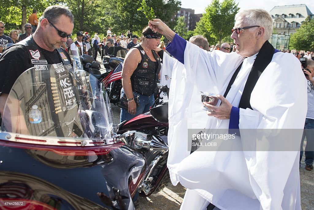 Rev. Gary Hall, Dean of the Washington National Cathedral, blesses riders and their motorcycles who will participate in Rolling Thunder during the Blessing of the Bikes at the Washington National Cathedral in Washington, DC, May 22, 2015. Clergy from around the region blessed the motorcycles and their riders prior to Monday's Rolling Thunder event, where thousands of motorcycles drive around the National Mall to honor prisoners of war (POWs) and missing in action (MIA) military members.