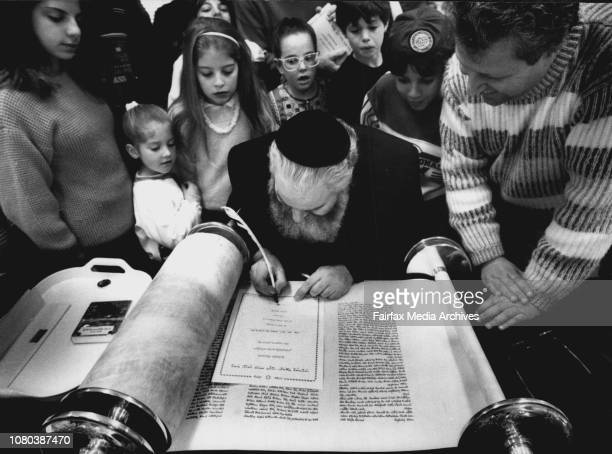 Rev. Gerald Blaivas fils out certificates for the assembled people who witnessed the signing of he Sefer Torah.***** finishing touches to a $40,000...