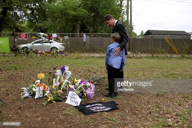 Rev. Jeremy Rutledge and his son look at a memorial built on the site where Walter Scott was killed by a North Charleston police officer, April 12,...