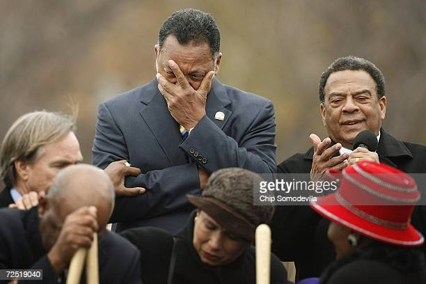 Rev Jesse Jackson covers his face while weeping as Ambassador Andrew Young gives an invocation at the groundbreaking of the Martin Luther King Jr...