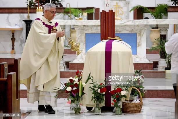 Rev. Julian Gerosa blesses the casket of Rosario Yanira Girón de Orellana of El Salvador, with incense during the funeral services at Christ the King...