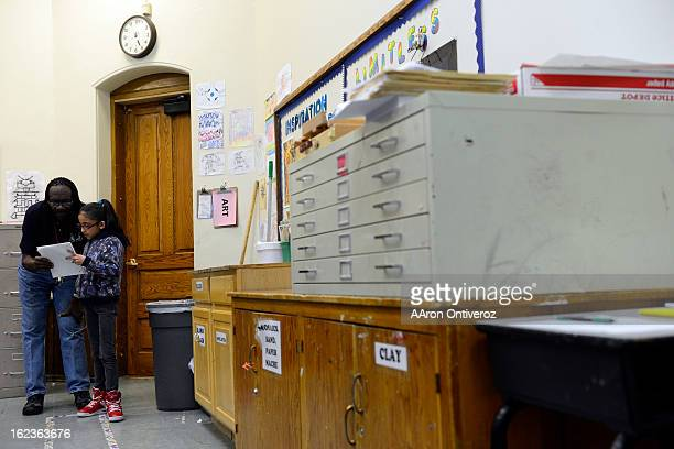Rev. Leon Kelly helps Fabiola Cordero with her homework during Open Doors after school program at Wyatt Elementary School. The program, which Kelly...