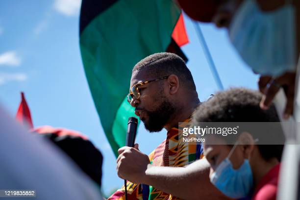 Rev Levi Combs III speaks to the crowd after climbing on the remaining base of where before a statue of Christopher Columbus stood to take the stage...