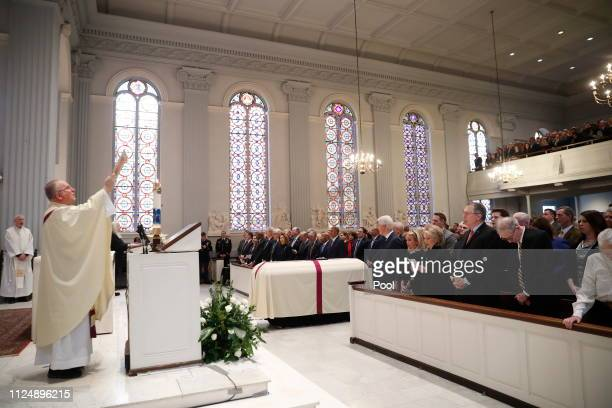 Rev Patrick Conroy holds up a bible during the Homily during funeral services for former Rep John Dingell on February 14 2019 at Holy Trinity...