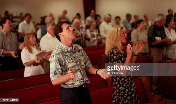 Rev. Robert A. Schuler, pastor at Rancho Capistrano Community Church, sings with his wife, Donna, right, and his congregation during a Sunday morning...