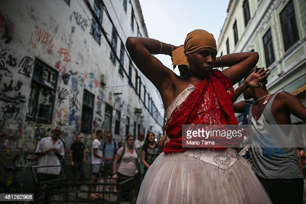 A reveler adjusts her traditional Bahian outfit during a 'Festas Juninas' marching performance by the street band 'Monobloco' on July 18 2015 in Rio...