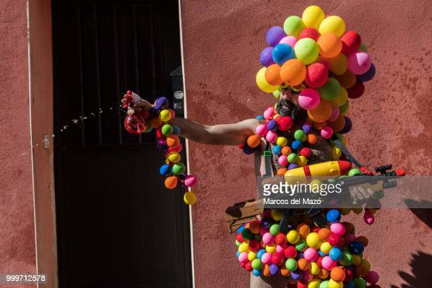 A reveler covered with balloons during the annual water fight known as 'Batalla Naval' in Vallecas neighborhood where thousands of people gathered to...