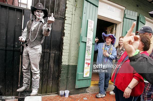 A reveler flips an obscene gesture at a street performer on Bourbon Street during Mardi Gras festivites February 6 2005 in New Orleans Louisiana...