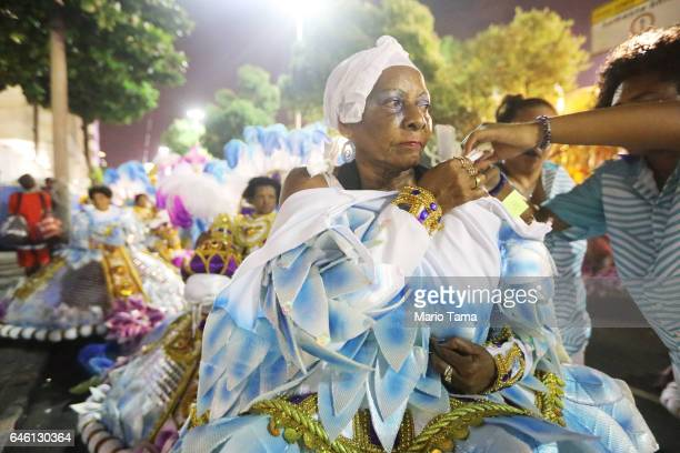 A reveler from the Portela samba school waits to perform outside the Sambodrome in the early morning hours during Carnival festivities on February 28...