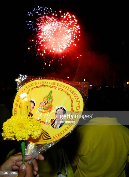 A reveler holds a fan and candle as fireworks go off in the distance during a ceremony to honor the King of Thailand the world's longest reigning...