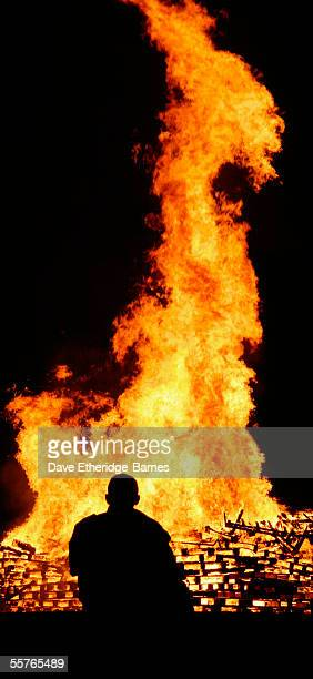 A reveler is seen standing by the bonfire during the first of the Bonfire Night celebrations on September 24 2005 in Burgess Hill England Bonfire...