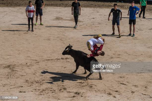 Reveler jumping over a bull after the first running of the bulls in the municipality of San Sebastian de los Reyes, near Madrid, also known as...