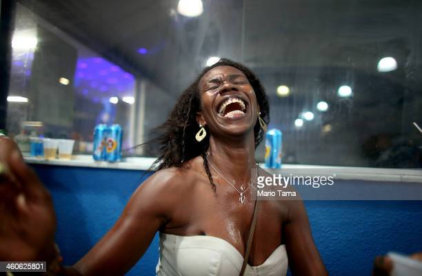 A reveler laughs while dancing at a traditional samba and feijoada party held at the Portela Samba School in the Madureira neighborhood during...