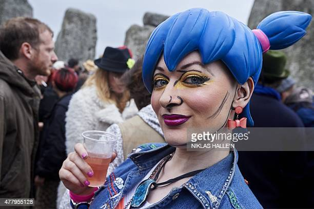 A reveler looks on as she and others celebrate the pagan festival of Summer Solstice at Stonehenge in Wiltshire southern England on June 21 2015 The...