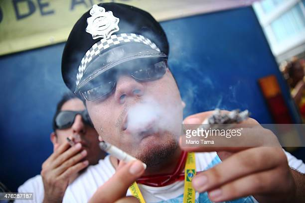 A reveler poses blowing smoke from multiple cigarettes during the 'Simpatia e Quase Amor' street carnival bloco along Ipanema Beach on March 2 2014...
