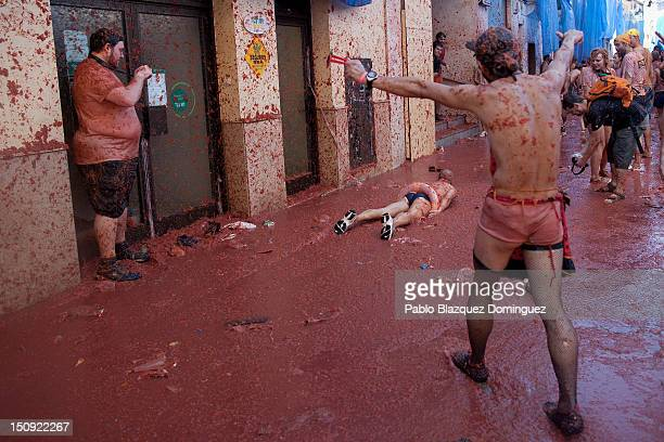 A reveler slides on tomato pulp while participating the annual Tomatina festival on August 29 2012 in Bunol Spain An estimated 35000 people throw 120...